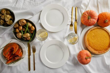 top view of served dinner with pumpkin pie, baked vegetables and fresh whole pumpkins on white tablecloth