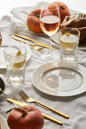 table with white tablecloth served with glasses of rose wine and lemon water, cutlery and whole pumpkins