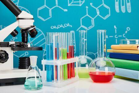 Mikroskop, Bücher, Glasröhrchen und Flaschen mit bunter Flüssigkeit auf blauem Hintergrund mit molekularer Struktur