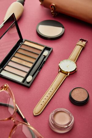 selective focus of watch near eye shadows and glasses on crimson
