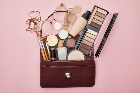 top view of brown bag near decorative cosmetics and watch isolated on pink