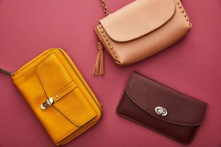 top view of leather and stylish bags isolated on crimson Stock Photo