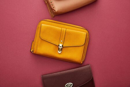 top view of stylish bags on crimson