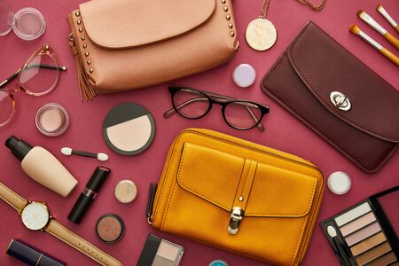 top view of stylish bags near decorative cosmetics isolated on crimson Stock Photo