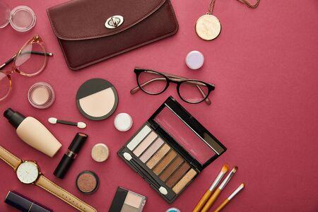 top view of brown bag near glasses and lipsticks on crimson