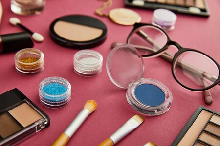 selective focus of cosmetic brushes near glasses on crimson