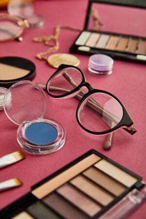 selective focus of glasses near decorative cosmetics on crimson