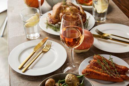 Cena festiva con verduras al horno, pavo a la parrilla y vasos con vino rosado en la mesa de piedra