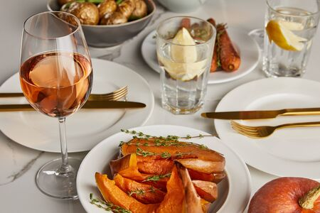 baked pumpkin and glasses with lemon water and rose wine on marble table Imagens