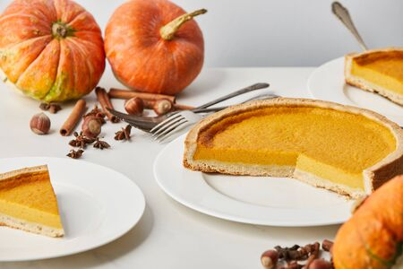 white plates with tasty pumpkin pie near whole pumpkins, cutlery and spices isolated on grey