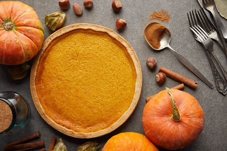 top view of delicious pumpkin pie near whole pumpkins, cutlery and hazelnuts on grey stone surface 写真素材