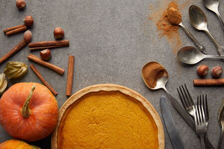 top view of tasty pumpkin pie near whole ripe pumpkin, cutlery, cinnamon and hazelnuts on grey stone surface