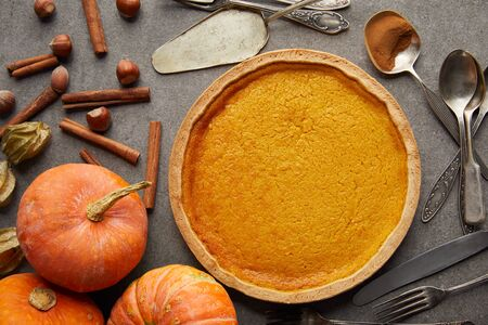 top view of delicious pumpkin pie near whole pumpkins, cutlery, hazelnuts and cinnamon sticks on grey stone surface