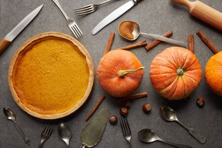 top view of tasty pumpkin pie near whole ripe pumpkins, cutlery, cinnamon sticks and hazelnuts on grey stone surface 写真素材