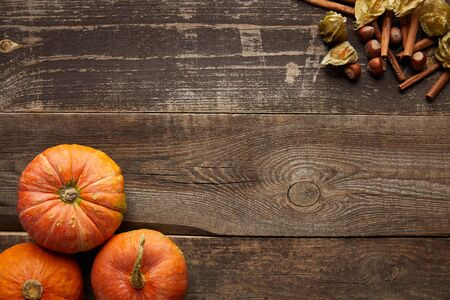 top view of fresh whole pumpkins near cinnamon sticks, hazelnuts and physalis on dark wooden surface with copy space