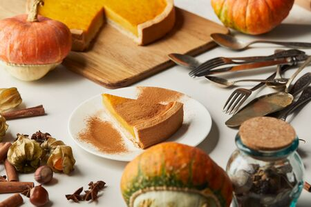 tasty pumpkin pie near whole pumpkins, cutlery and spices on white surface