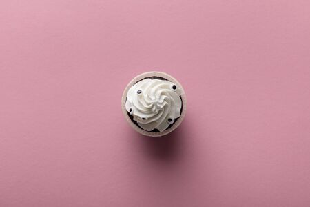 top view of delicious Halloween cupcake with white cream on pink background