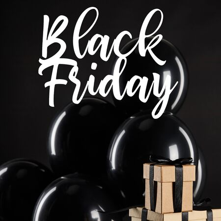 bunch of black balloons near stack of gift boxes isolated on black with black Friday illustration 写真素材