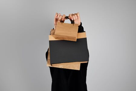 woman with obscure face holding paper shopping bags isolated on grey, black Friday concept
