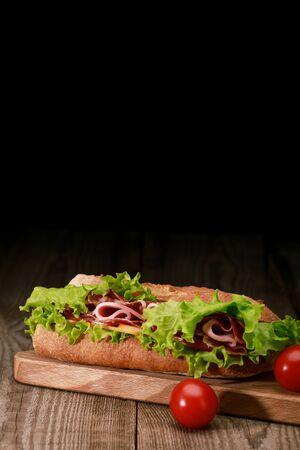 Sándwich fresco con lechuga, jamón, queso, tocino sobre tabla de cortar de madera con tomates cherry aislados en negro