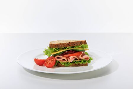 fresh sandwich with lettuce, ham, cheese, bacon and tomato on plate isolated on white Foto de archivo - 133651186
