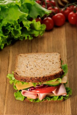 selective focus of fresh sandwich on wooden cutting board near lettuce and cherry tomatoes Foto de archivo - 133650997