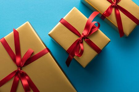 top view of golden gift boxes with red ribbons and bows on blue background