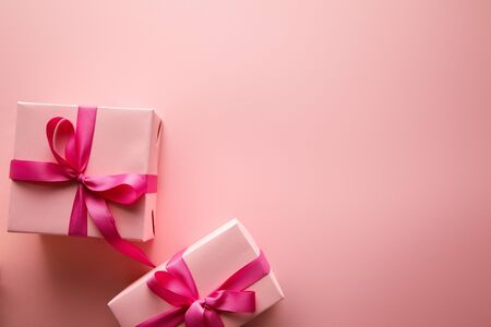 top view of gift boxes with satin ribbons on pink background Imagens