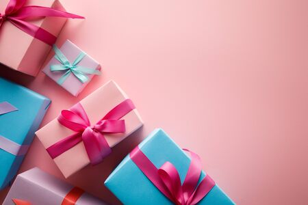 top view of colorful gift boxes with satin ribbons on pink background