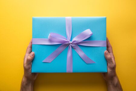 cropped view of man holding blue gift box with violet ribbon on yellow background Imagens