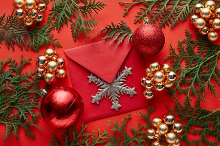 top view of shiny Christmas decoration, envelope with snowflake and thuja on red background