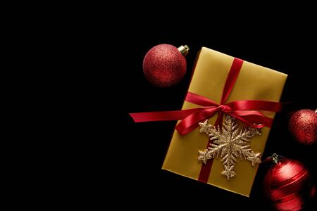top view of shiny golden Christmas gift with red ribbon and snowflake near baubles isolated on black Stock Photo