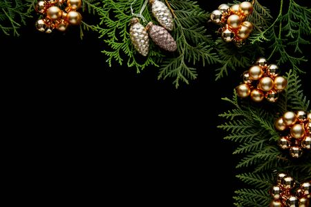 top view of shiny golden Christmas decoration on green thuja branches isolated on black with copy space