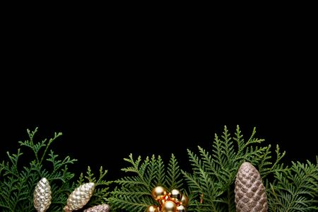 top view of shiny golden Christmas decoration, green thuja branches isolated on black with copy space Stock Photo