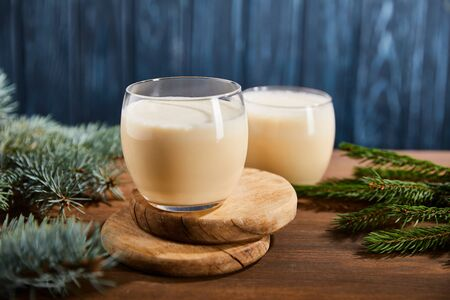 delicious eggnog cocktail on round wooden boards near spruce branches on blue textured background