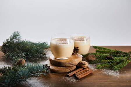 flavored eggnog cocktail on round boards, spruce branches, cinnamon sticks and walnuts isolated on grey Standard-Bild
