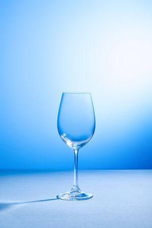 leeg, schoon en kwetsbaar glas op blauwe achtergrond met kopieerruimte
