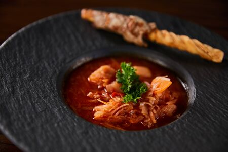 close up view of traditional ukrainian borscht garnished with parsley in black plate