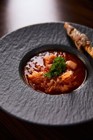 traditional ukrainian borscht garnished with parsley in black plate