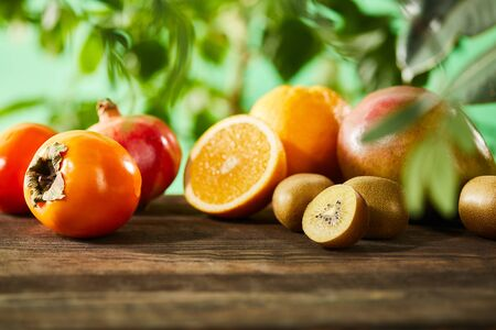 selective focus of kiwi, oranges, pomegranate, mango and persimmons on wooden table