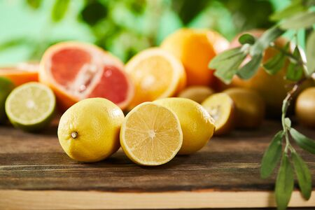 selective focus of cut and whole lemons on wooden surface