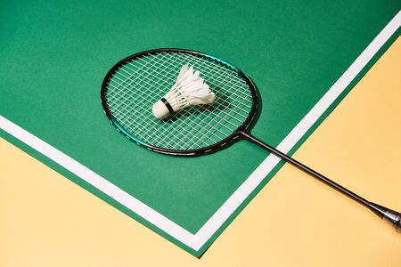 Metal badminton racket and shuttlecock on green and yellow surface with line Stock Photo