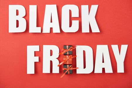 top view of black friday white lettering with small presents on red background