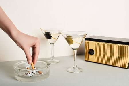 Cropped view of woman putting cigarette to ashtray beside cocktails and vintage radio on white background 写真素材