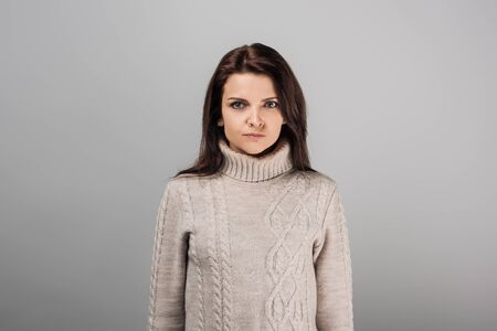 displeased woman in sweater looking at camera isolated on grey Reklamní fotografie