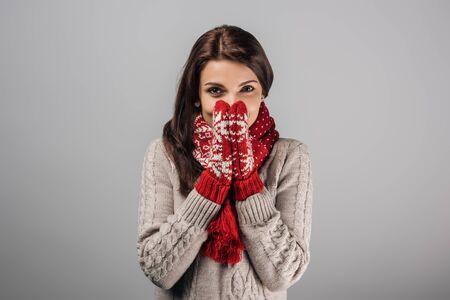 Frau in roten Handschuhen und Schal bedeckt Gesicht isoliert auf grau Standard-Bild