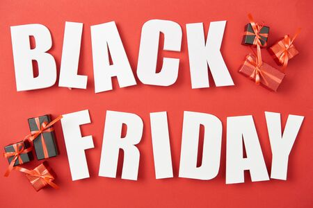 top view of black friday white lettering near small presents on red background Stockfoto