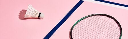Badminton racket and shuttlecock on pink background with blue lines, panoramic shot