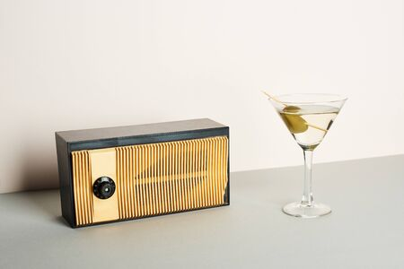 Vintage radio with glass of martini cocktail on grey surface