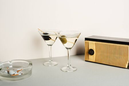 Martini cocktails with ashtray and cigarette butts and vintage radio on white background 写真素材
